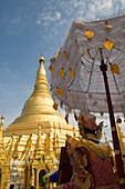 Figure under a sunshade on the grounds of the Shwedagon Pagoda at Yangon, Rangoon, Myanmar, Burma