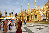 Buddhistic monk and tourists in front of golden stupas on the grounds of the Shwedagon Pagoda at Yangon, Rangoon, Myanmar, Burma