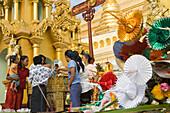 Buddhistic believers with oblations in the Shwedagon Pagoda at Yangon, Rangoon, Myanmar, Burma