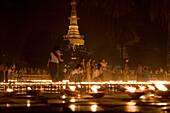 Buddhistic believers lighting candles at the Botataung Pagoda at night, Yangon, Rangoon, Myanmar, Burma