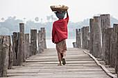 Burmese women, seen from behind carrying a basket on her head while  walking on the U Beins Bridge in Amarapura near Mandalay, Myanmar, Burma