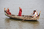 Buddhistic monks in a rowing-boat on Taungthaman Lake in Amarapura near Mandalay, Myanmar, Burma