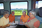 Group of senior people reading a map during a train journey, Allgau, Bavaria, Germany