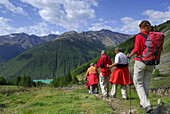 Group of hikers descending from alpine lodge Similaunhuette to reservoir Vernagtsee, Oetztal range, South Tyrol, Italy