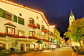 Gasthof, Kirche und Fußgängerzone in Sterzing, beleuchtet in der Dämmerung, Sterzing, Südtirol, Italien