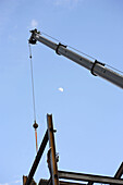 Construction steel iron worker high on building with crane raising steel I beam
