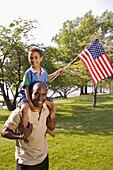 Afroamerikaner, Aktivität, Amerika, amerikanische Fahne, Auf dem Rücken, Auf Schulter, Aussen, Bande, Blick Kamera, Draussen, Erholen, Erholung, Erwachsene, Erwachsener, Ethnisch, Fahne, Fahnen, Familie, Familien, Farbe, Flagge, Flaggen, Freizeit, Freude,