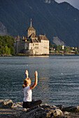 Woman exercising yoga at the shore of Lake Geneva, Chillon Castle in the background, Veytaux, Vaud, Switzerland