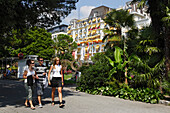Young people walking along promenade, Grand Hotel Suisse in background, Montreux, Canton of Vaud, Switzerland