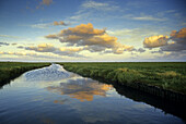 A canal in the tidal land reflecting clouds, Eiderstedt peninsula, North Friesland, Schleswig-Holstein, Germany