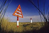 Warning sign and lighthouse at Westenellenbogen, Sylt island, North Friesland, North Sea, Schleswig-Holstein, Germany