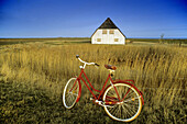 Bicycle in front of a house on dwelling mound, Langeness Hallig, Schleswig-Holstein, Germany