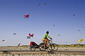 Kites at the beach, cyclists in foreground, St. Peter-Ording, Schleswig-Holstein, Germany