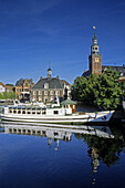 Excursion boat passing town hall and historic building Waage, Leer, Lower Saxony, Germany