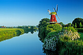 Windmill at a canal under blue sky, Greetsiel, East Friesland, Lower Saxony, Germany