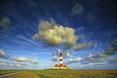 Westerhever lighthouse under cloudy sky, Eiderstedt peninsula, North Friesland, North Sea, Schleswig-Holstein, Germany