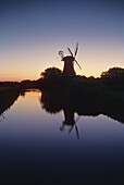 Windmill at a canal in the afterglow, Greetsiel, East Friesland, Lower Saxony, Germany