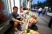 Smiling street hawker is sitting in front of his fruitbag in Chongqing, China, Asia