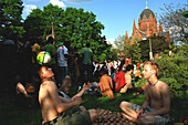Group of young people sitting in a park near the Holy Cross Church, Berlin, Germany