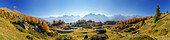 Panorama in Unterengadin with larches in autumn colours and range of Unterengadiner Dolomiten with Piz Lischana, Piz Pisoc, Piz Zuort, Piz Plavna, Piz Nuna and Piz Macun, Unterengadin, Engadin, Grisons, Switzerland