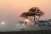 A person and three all-terrain vehicles in front of the setting sun, Al Hajar mountains, Oman, Asia, Oman, Asia