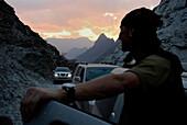 A man and all-terrain vehicles at dawn, Al Hajar mountains, Oman, Asia