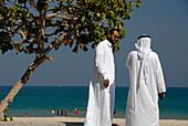 Two local men in front of the beach, Al Fujairah, United Arab Emirates