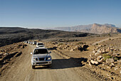 A row of all-terrain vehicles driving on a road through barren scenery, Al Hajar mountains, Oman, Asia