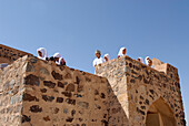 Local children looking at view from the battlements of Fort Jabrin, Oman, Asia