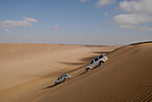 Two all-terrain vehicles driving down a sand dune, Wahiba Sands, Oman, Asia
