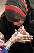 Local woman painting a tourist's hand with henna, Djamâa el-Fna square, Marrakesh, Morocco, Africa