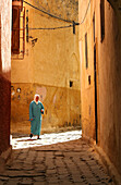 Moroccan woman at an alley of Meknes' medina, Meknes, Morocco, Africa