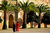 Two moroccan women in front of the fortification wall of the royal palace Dar el Makhezen, Meknes, Morocco, Africa