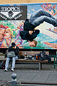 Teenager performing a somersault, Young man sitting with his laptop, Leisure, Ingolstadt, Bavaria, Germany
