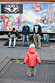 Small child standing in front of teenagers, youths, playground, Ingolstadt, Bavaria, Germany