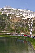 Zug fährt am See vorbei, Berglandschaft, Furka Pass, Schweiz