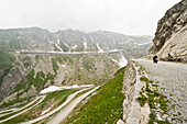 Person driving a scooter on a mountain pass, Mountain landscape with tunnel, St. Gotthard, Switzerland