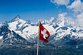 Swiss flag in a mountainous landscape, Valais, Switzerland