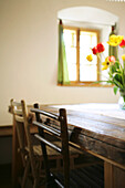 Two rusti chairs made of wood at a woodtable with a bouquet of red and yellow tulips