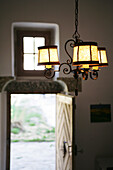 Fresh air and the view into a garden, illuminated, antique lamp and an open door