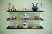 Decorated souvenir shelf with antique asian teapot, cups
