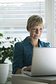 Mature woman using a laptop, Styria, Austria