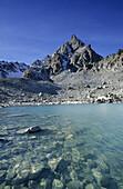 Moraine lake with Piz Kesch, Silvretta range, Upper Engadin, Grisons, Switzerland