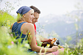 Young couple having a picnic, Werdenfelser Land, Bavaria, Germany