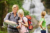 Hikers reading map, Werdenfelser Land, Bavaria, Germany