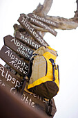 Backpack and sign post, Wetterstein range, Bavaria, Germany