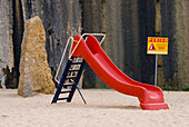 Red slide in a playground with danger sign, Ericeira, Portugal, Atlantic
