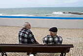 Two older men, fishermen, sitting on a bench, Seaview, Ericeira, Portugal, Atlantic