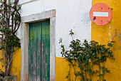 Yellow and white painted house with No entry sign, Old town of Obidos, Leiria, Estremadura, Portugal