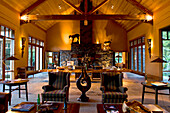 Cosy armchairs standing at the ample lounge of the Treetops Lodge, North Island, New Zealand, Oceania